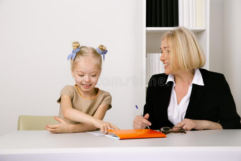 Picture of female tutor helping little girl. Teacher and pupil concept. stock photos