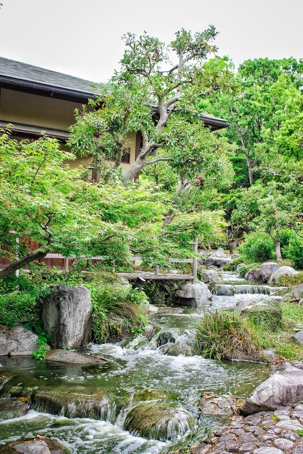 Picture of flowing river with stone rock formation next to Japanese Traditional House located in Tsurumi Ryokuchi Park, Japan royalty free stock image