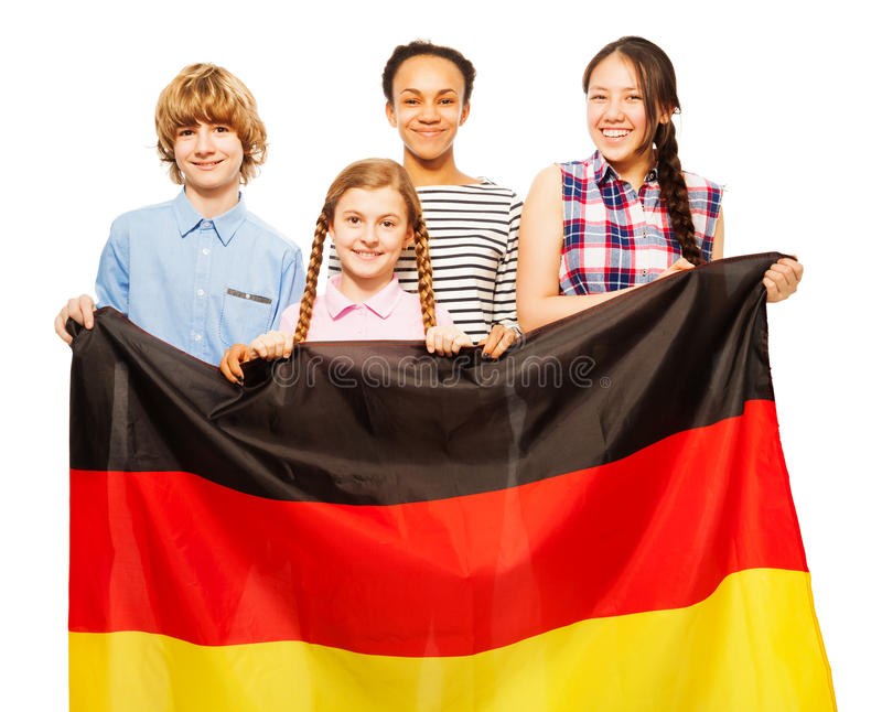 Picture of four teenage kids holding German flag. Picture of four smiling teenage kids holding German flag, standing behind it, isolated on white royalty free stock images