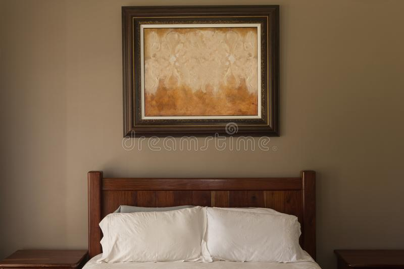 Picture frame in bedroom at home. Front view of a modern picture frame fixed above the bed in bedroom at home stock photography