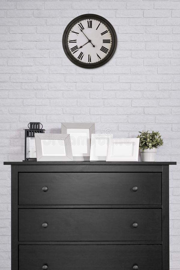 picture frames collages on black wooden cabinet and clock in empty room with white brick wall background, vintage style stock photos