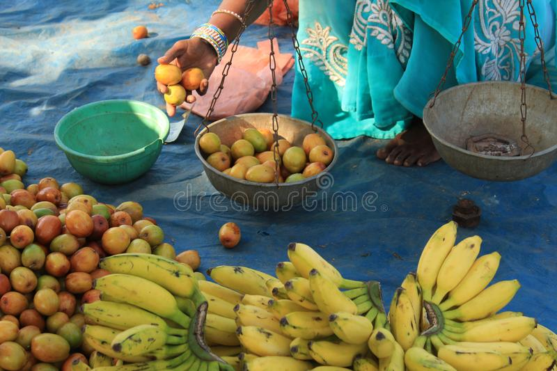 Fruit Vendor Selling plum at Street. Picture of a Fruit Vendor selling plum on traditional weight machine  at Chitrakot Waterfall street side stock photo