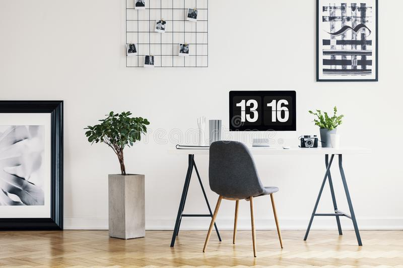 Picture gallery and a concrete planter in a simple home office interior for a freelancer professional with a computer screen mock- stock image