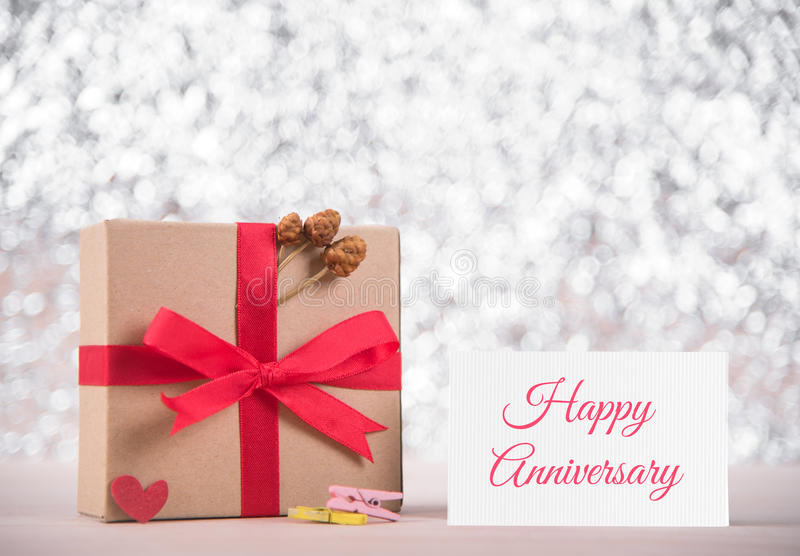 Picture of gift box with red ribbon and message happy anniversary on greeting card, blur bokeh gray background. congratulation co stock photos