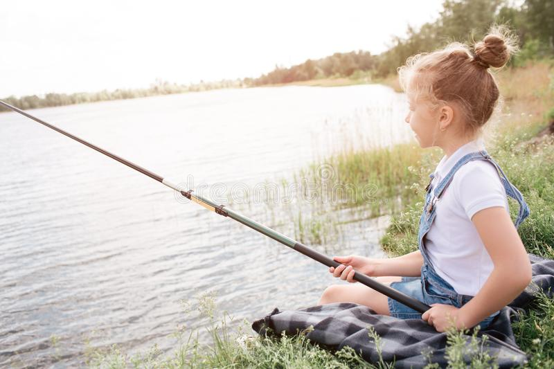 A picture of girl sitting alone at river shore. She is fishing. Girl is holding fish-rod with both hands. She is looking stock photos