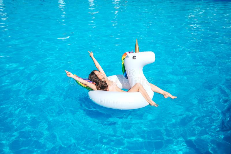 A picture of girl swimming in pool alone. She lies on air mattress and poses. Girl os resting. She has some fun. A picture of girl swimming in pool alone. She stock image