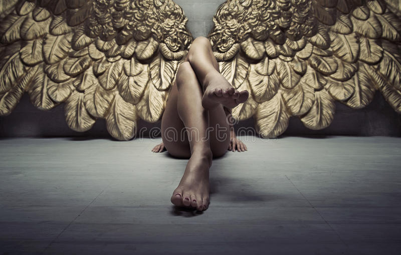 Picture of gold angel relaxing on the floor. Picture of a gold angel relaxing on the floor stock photo