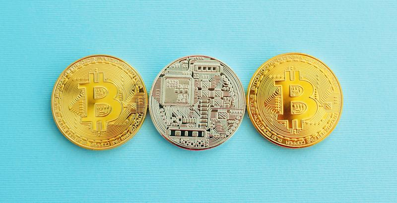 Picture of three gold bitcoin over blue background. Digital money concept royalty free stock photos