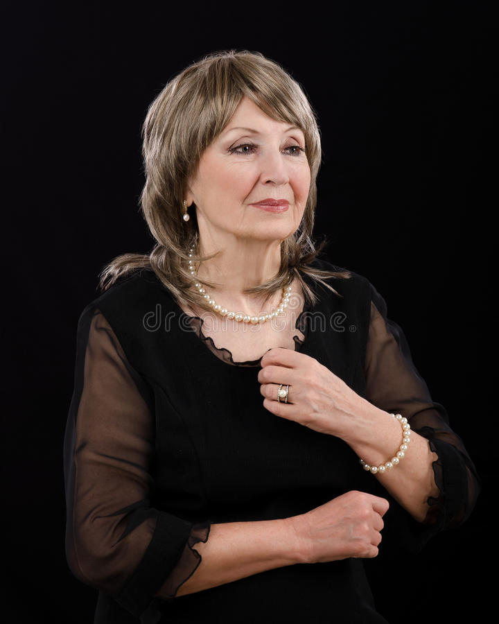 Picture of gorgeous older woman posing with imitation pearl set. Half-length portrait of gorgeous 76-year-old woman with imitation sea pearl set. She is wearing stock images