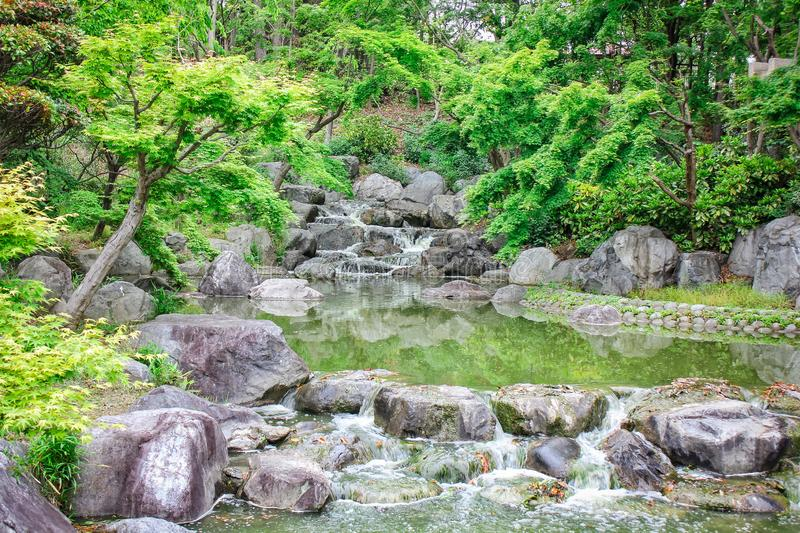 Picture of green, calming, refreshing lake with stone rock formation and trees located as one travel tourism destination in Osaka. Picture green calming royalty free stock photos