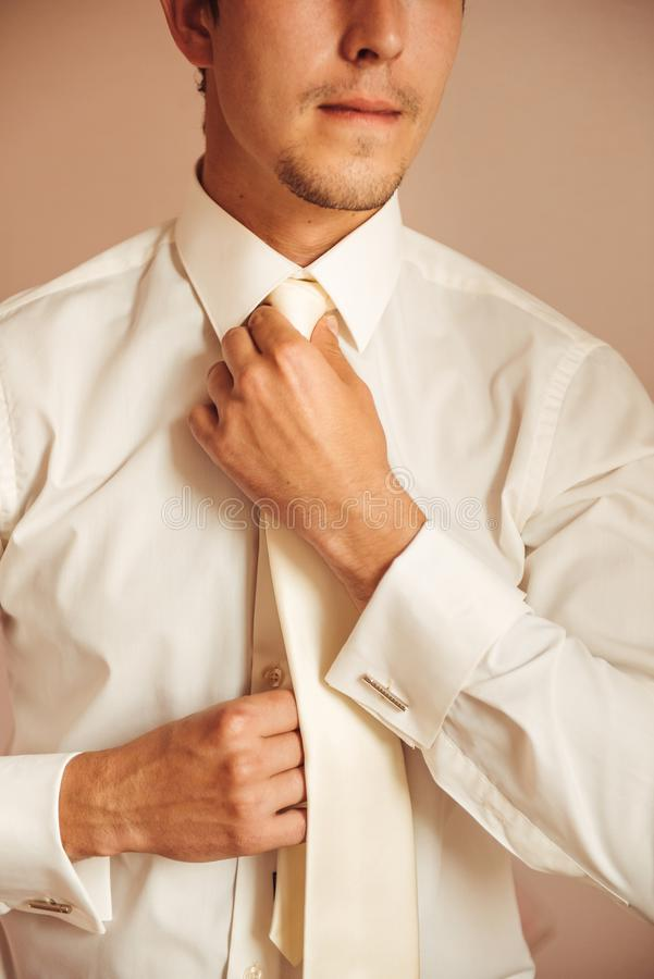 Picture of a groom fixing a fine tie carefully stock images