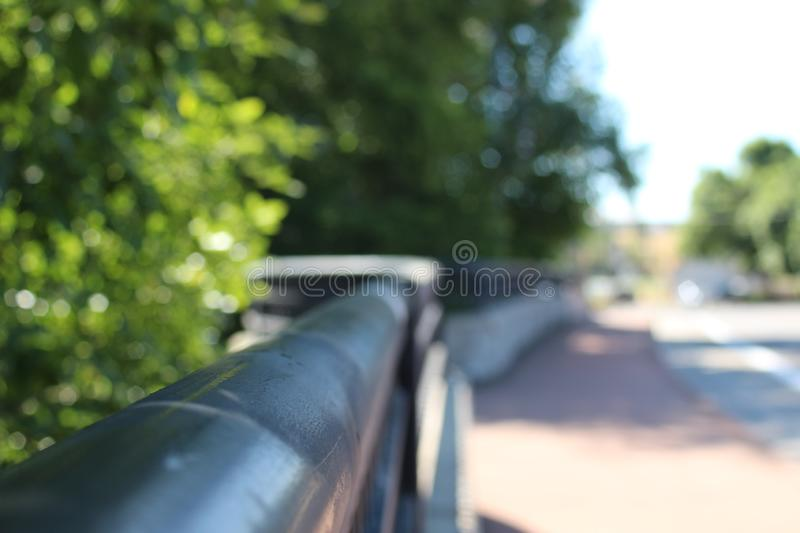 A picture of the handrail from the bridge going over the creek stock photography