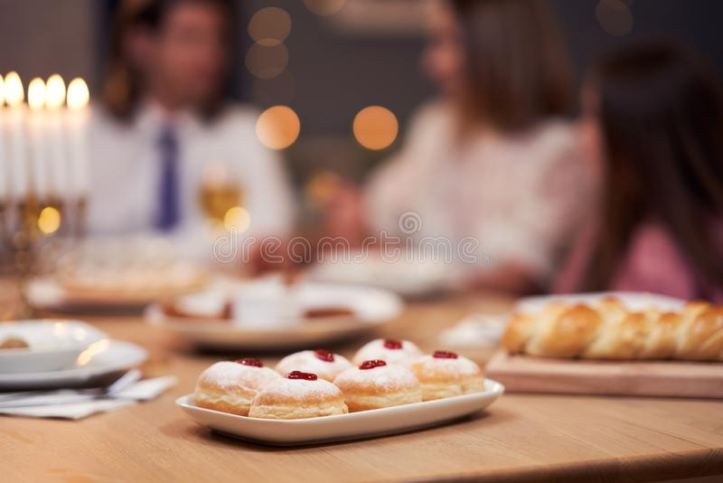 Hanukkah dinner. Family gathered around the table with traditional dishes stock images