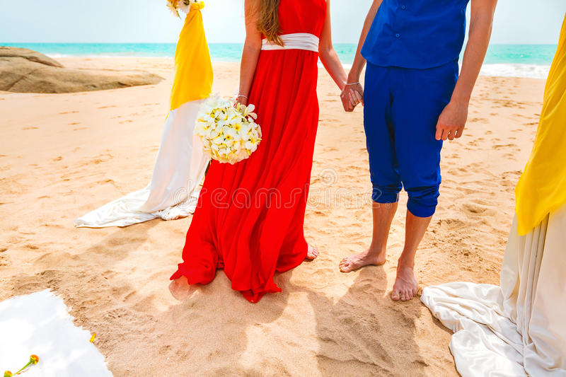 A picture of a happy couple holding hands at the beach. Newlyweds at the honeymoon. Close-up stock photography