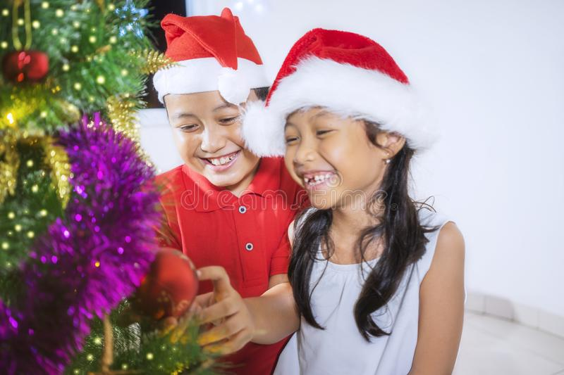 Happy girl with her brother decorates Christmas tree royalty free stock photo