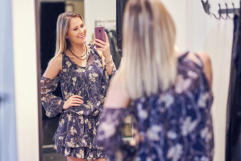 Happy woman shopping for clothes in store. Picture of happy woman shopping for clothes in store stock image