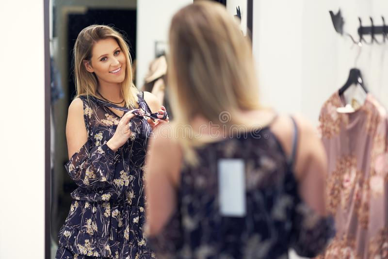 Happy woman shopping for clothes in store. Picture of happy woman shopping for clothes in store royalty free stock images