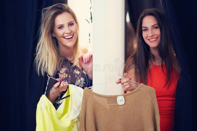 Happy woman shopping for clothes in store. Picture of happy women shopping for clothes in store stock photos