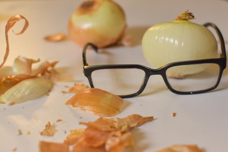 Close up of black eye glasses with a peeled onion with onion skin on white background royalty free stock photo