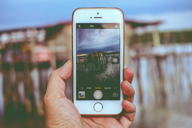 Picture Holding Iphone Taking Photo on House on Beach stock photography