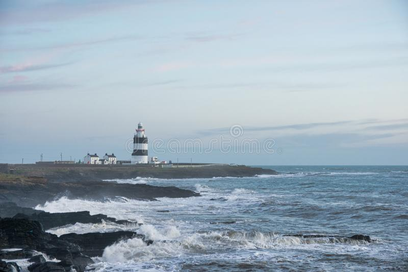 Light House on Rocky Coast. This is a picture of Hook Light House in County Wexford, Ireland. It was taken at sunset. The waves were crashing onto the rocks stock images