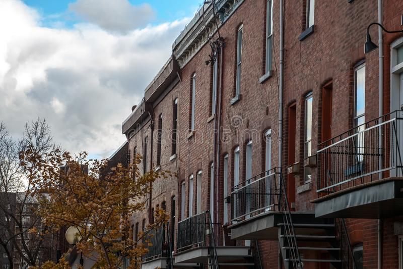 Facades of traditional North American residential buildings, red brick houses, taken in the center of Montreal. Picture of houses of Montreal, Quebec, Canada stock photo