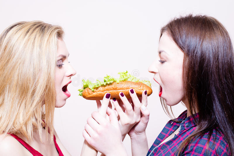 Picture of 2 hungry beautiful girls having fun royalty free stock photography