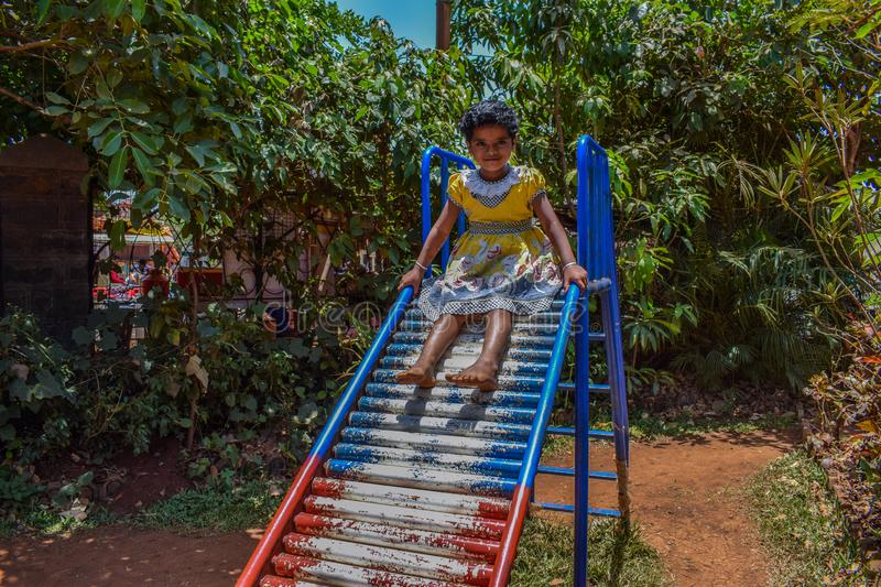 Picture of a Indian kid playing on slider in a park. Indian kid playing on slider in a park in her holiday royalty free stock photo