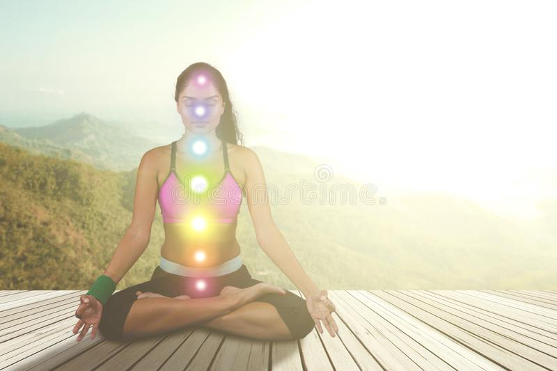 Woman meditating with colored chakra points stock images