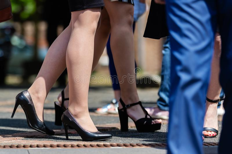 Legs of elegant clothed women standing outdoors. Picture of legs of elegant clothed women standing outdoors stock images