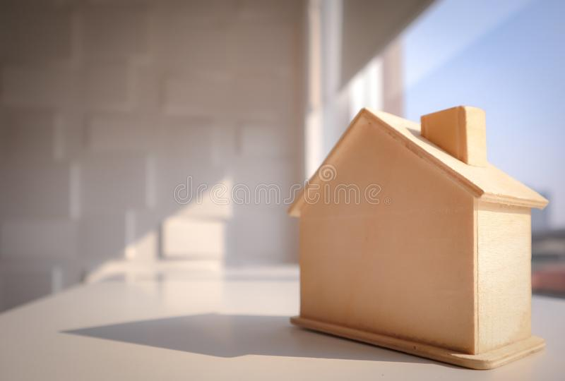 Picture of light brown wooden model home on the table with the background of cityscape and sky stock photos