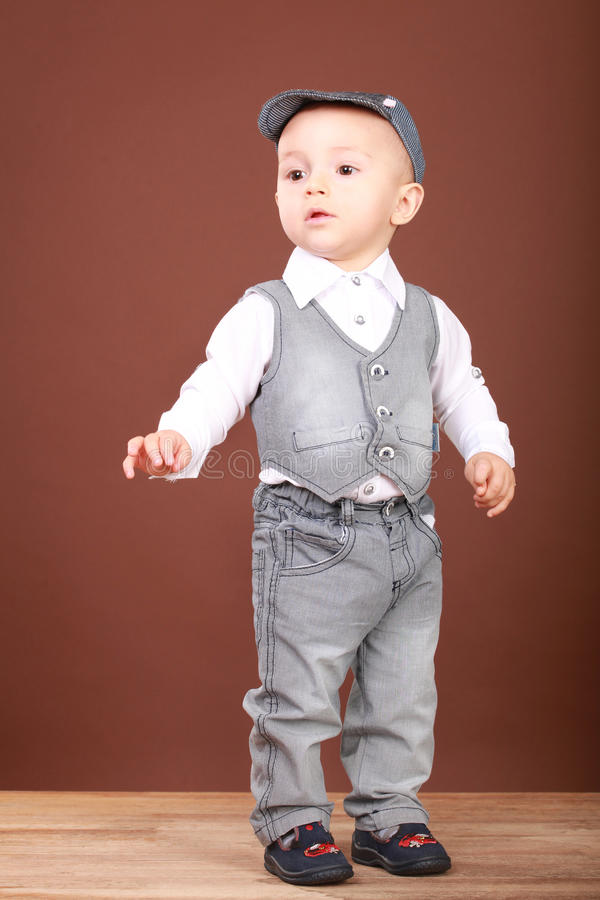 Picture of a little boy in denim suit and a cap royalty free stock image