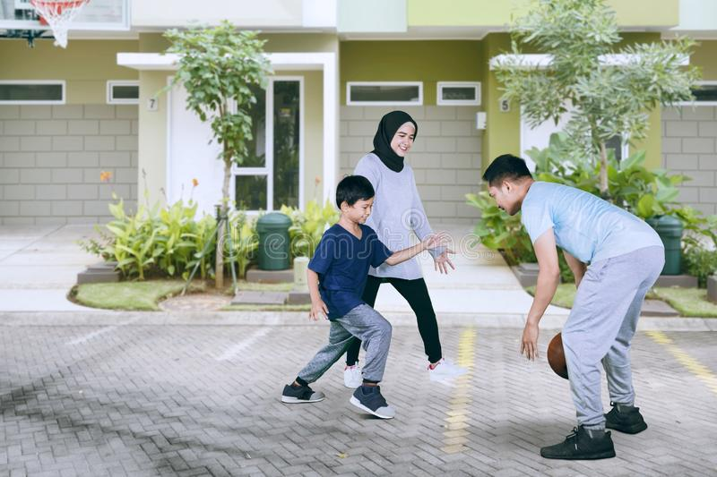 Little boy playing basketball with his parents stock images