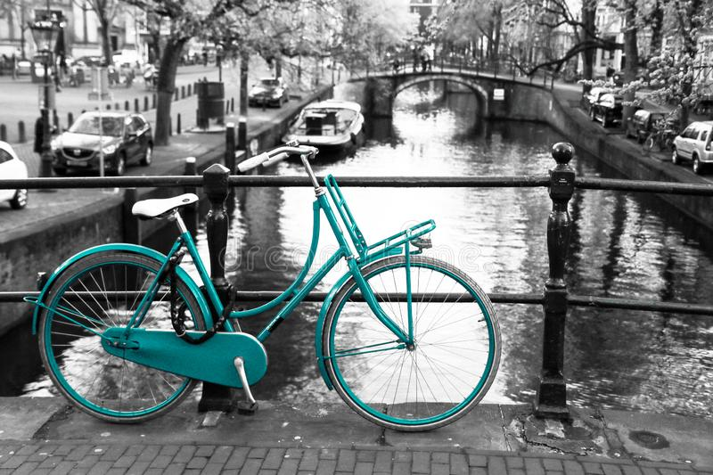 Lonely azure bike in Amsterdam. A picture of a lonely azure bike on the bridge over the channel in Amsterdam. The background is black and white stock images