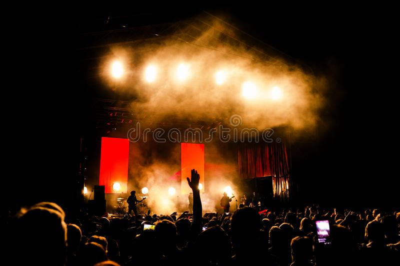 Picture of a lot of people enjoying night perfomance, large unrecognizable crowd dancing with raised up hands and mobile phones on. Concert. nightlife stock photography