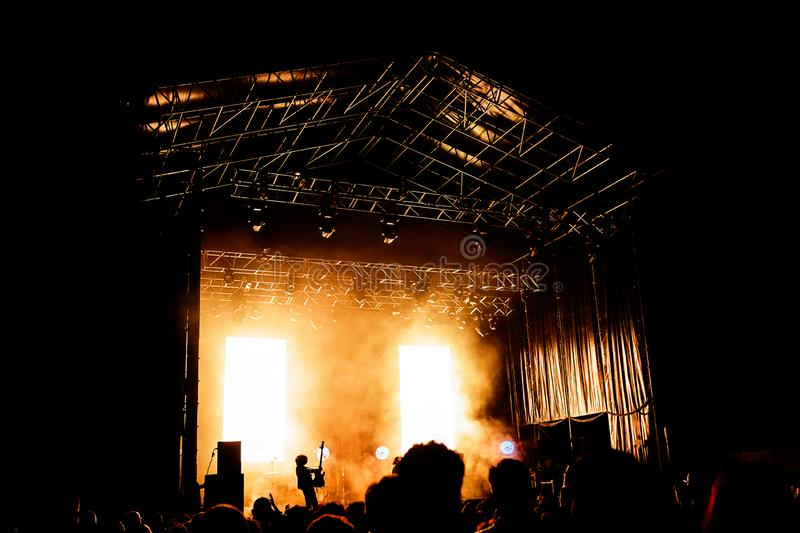 Picture of a lot of people enjoying night perfomance, large unrecognizable crowd dancing with raised up hands and mobile phones on. Concert. nightlife royalty free stock photo