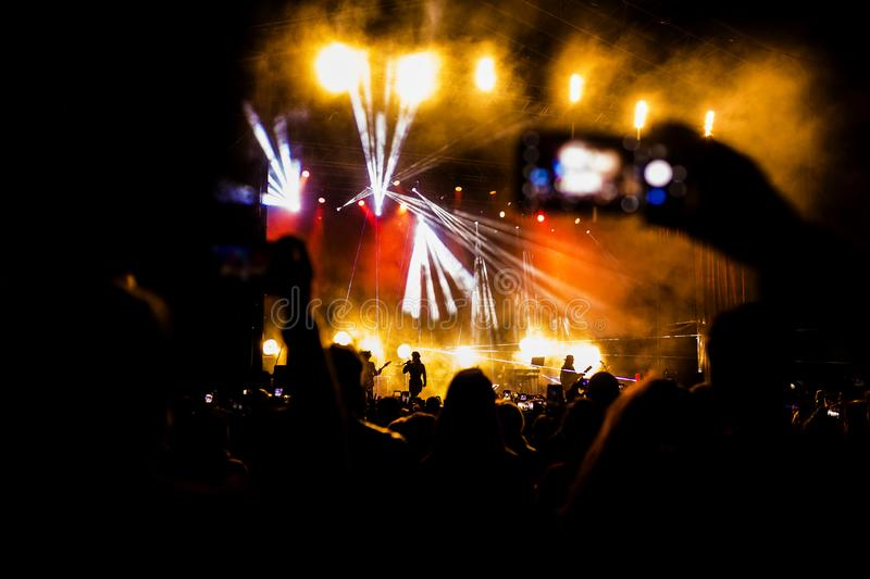 Picture of a lot of people enjoying night perfomance, large unrecognizable crowd dancing with raised up hands and mobile phones on. Concert. nightlife stock image