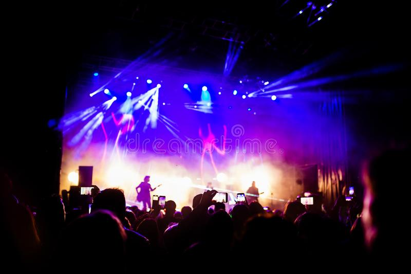 Picture of a lot of people enjoying night perfomance, large unrecognizable crowd dancing with raised up hands and mobile phones on. Concert. nightlife stock photos
