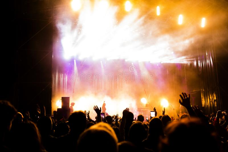 Picture of a lot of people enjoying night perfomance, large unrecognizable crowd dancing with raised up hands and mobile phones on. Concert. nightlife royalty free stock image