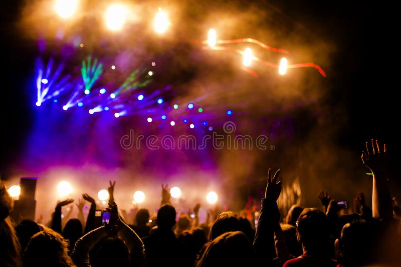Picture of a lot of people enjoying night perfomance, large unrecognizable crowd dancing with raised up hands and mobile phones on. Concert. nightlife royalty free stock photography