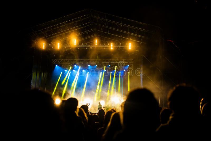 Picture of a lot of people enjoying night perfomance, large unrecognizable crowd dancing with raised up hands and mobile phones on. Concert. nightlife royalty free stock photos