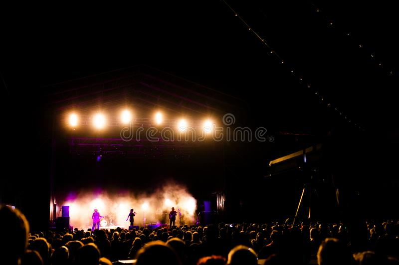 Picture of a lot of people enjoying night perfomance, large unrecognizable crowd dancing with raised up hands and mobile phones on. Concert. nightlife stock images