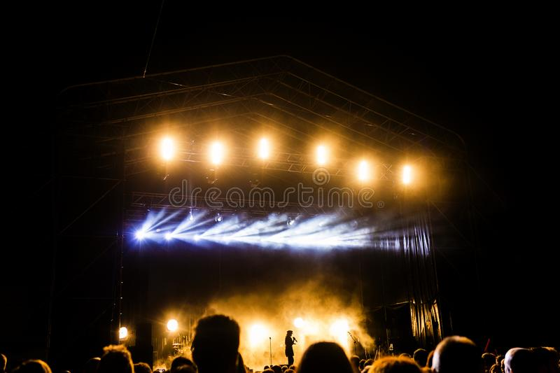 Picture of a lot of people enjoying night perfomance, large unrecognizable crowd dancing with raised up hands and mobile phones on. Concert. nightlife royalty free stock images