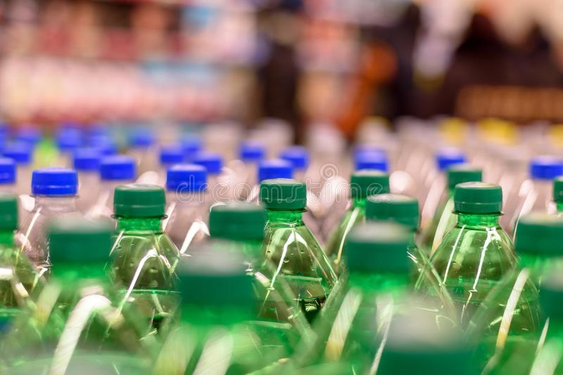 Picture lots of green bottles with the soda you only see the cover, selective focus royalty free stock photos