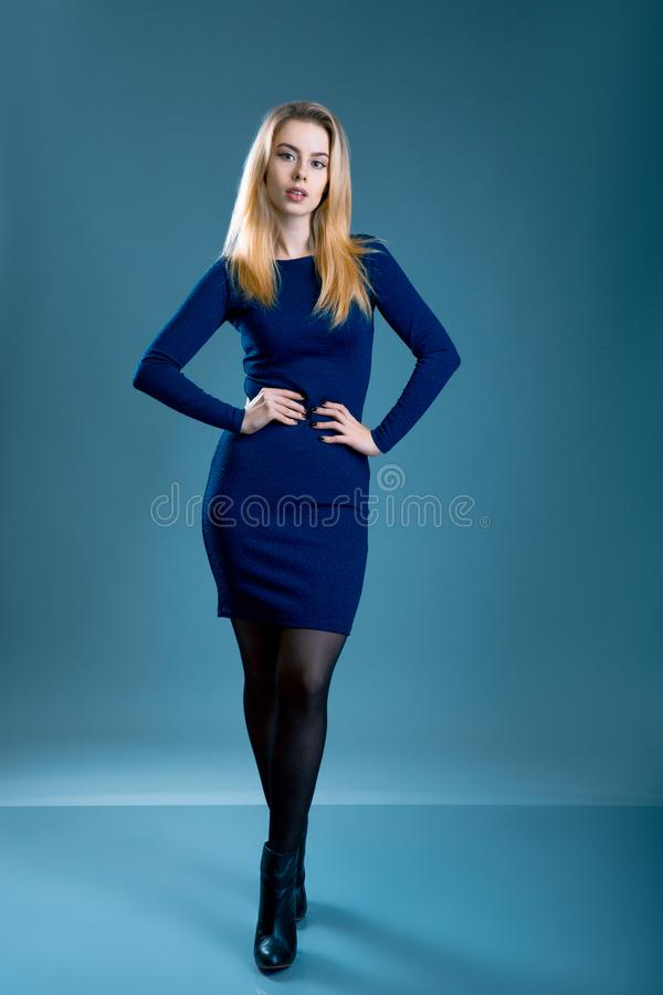 Picture of lovely woman in blue dress over gray bleu background royalty free stock photos