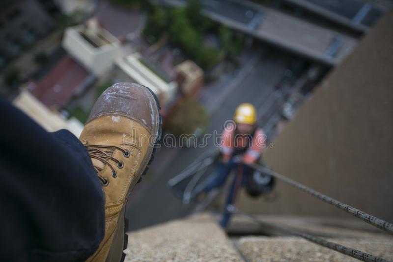 Picture of male leg setting on the edge of building site wearing blue pant, steel cape working safety boot with blurring construct royalty free stock photos