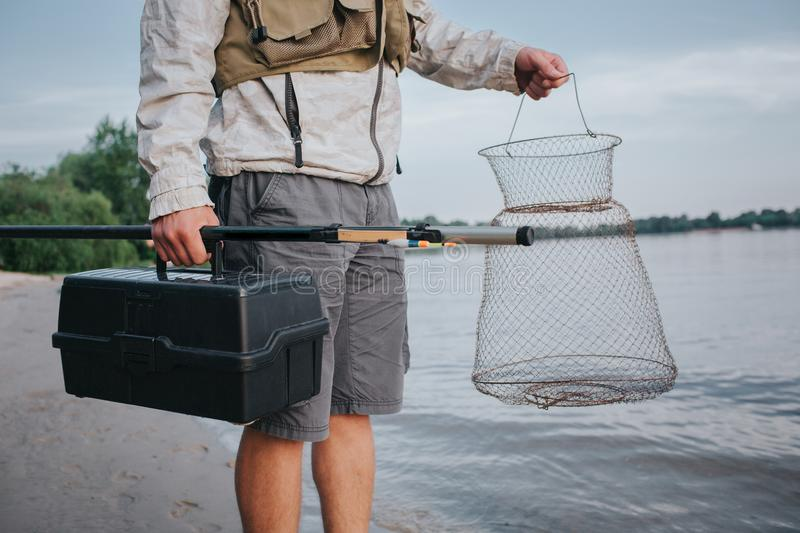 A picture of man holding fishing net and plastic black box in hands. Also he has fly rold in the right one. Guy is. Standing at the watr shore stock photography