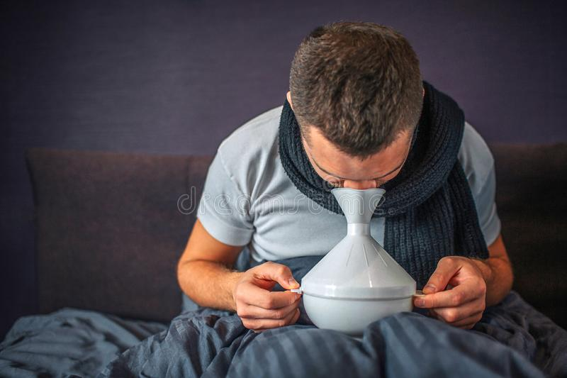 Picture of man using inhaler for treatment and for getting better. He is sick and ill. Guy holds white thing careful and royalty free stock photos