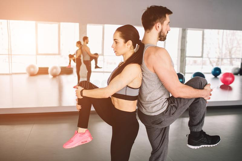 A picture of man and woman standing back to back and pulling up one leg. They are trying to keep the balace of bodies on stock images