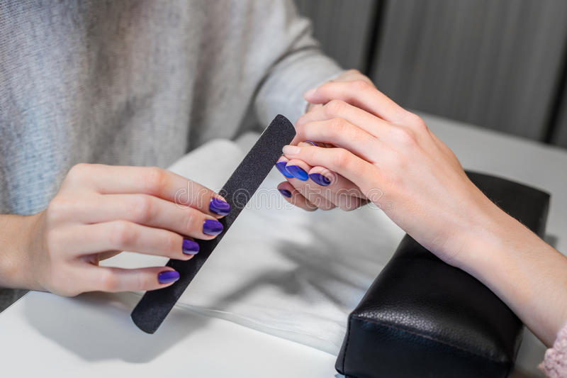 Picture of manicure process on female hands. Closeup picture of manicure process on female hands in beauty nail salon. Manicurist nail file works royalty free stock images